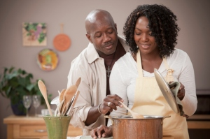 A husband stirring a pot in his kitchen while his wife observes