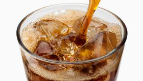 A stream of diet cola pouring into a glass