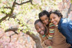 A smiling father, mother and daughter standing beside a blooming cherry blossom tree