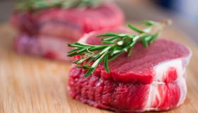 Two pieces of raw beef tenderloin with rosemary on a wooden block surface