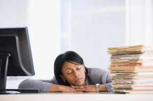 A woman sleeping at her desk