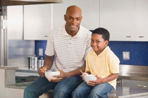 A father and his son sitting in kitchen and eating from bowls