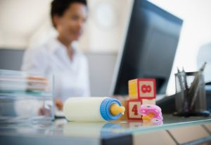 A baby bottle and blocks on businesswoman's desk