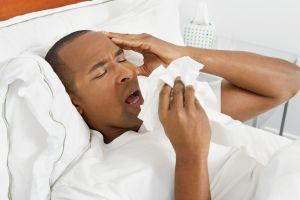 A man sneezing into tissues in bed