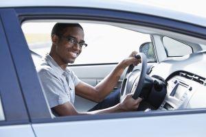 A teenaged male driving a car