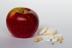 An apple sitting beside a group of vitamins