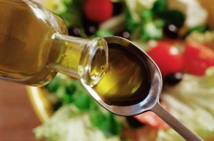 Olive oil pouring onto a spoon over a salad