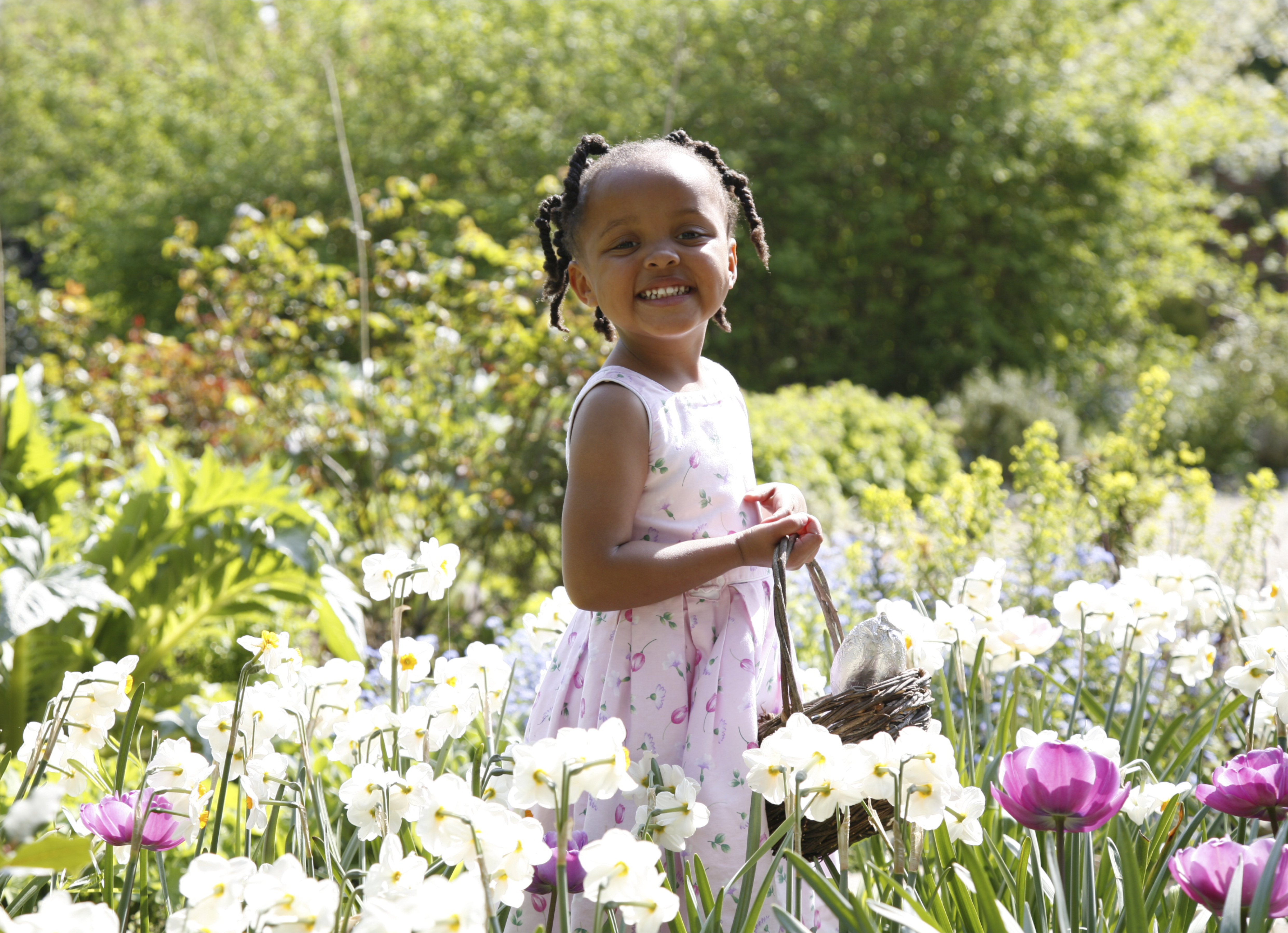 A little smiling girl with an Easter basket standing in a garden