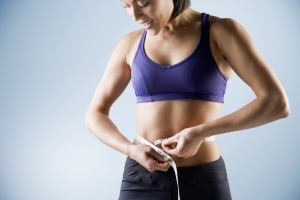 A woman measuring her waist