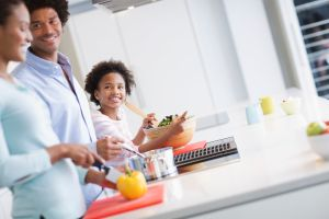 A smiling family cooking in their kitchen