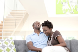 A laughing couple sitting on sofa in living room