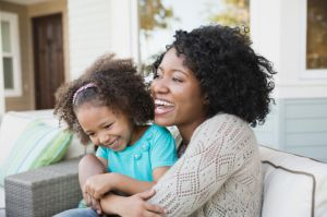 Happy mother embracing daughter on outdoor sofa