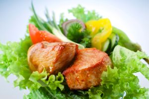 Pieces of roasted pork on salad