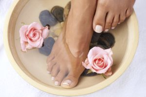 A pair of pedicured feet soaking in water in a bowl with pink roses