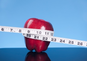An apple with a tape measure wrapped around it
