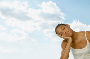 A woman with eyes closed leaning head in hand, with clouds in background