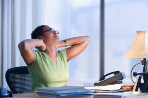 A woman stretching her neck at her desk