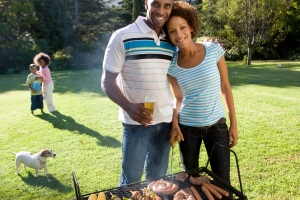 A smiling family barbecuing in their backyard