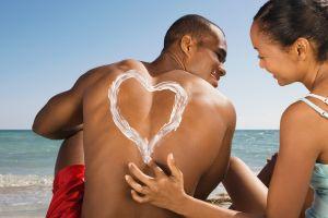 A woman drawing a heart in sunscreen on boyfriend's back