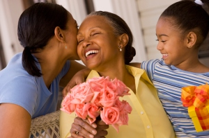 An adult daughter and her little daughter kissing a grandmother on Mother's Day