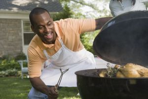 Smiling man cooking food on grill outdoors