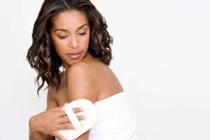 Woman buffing skin with an exfoliating mitt