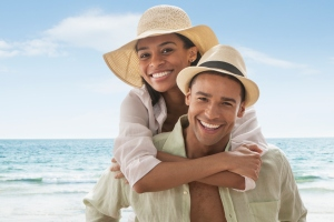 Smiling man carrying girlfriend on beach