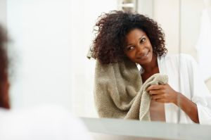 A woman towel drying her hair as she smiles in front of a mirror