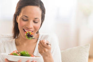 A Woman Eating Fresh Salad At Home