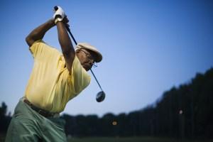 A senior man swinging a golf club