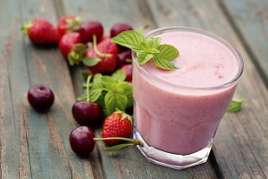 A berry smoothie in a glass surrounded by berries and cherries