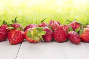 Strawberries on white wooden table in sunny garden