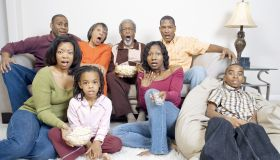 A large family watching TV in their living room