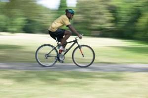 A man biking fast on a bike path in the park
