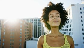 A woman smiling with her eyes closed on a rooftop