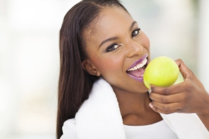 A smiling woman eating an apple