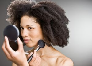 A woman applying makeup powder with compact and brush