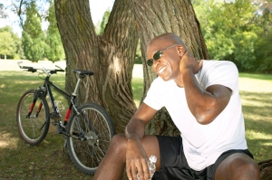 A biker resting against a tree and rubbing his neck