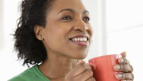 Woman holding mug smiling, close-up