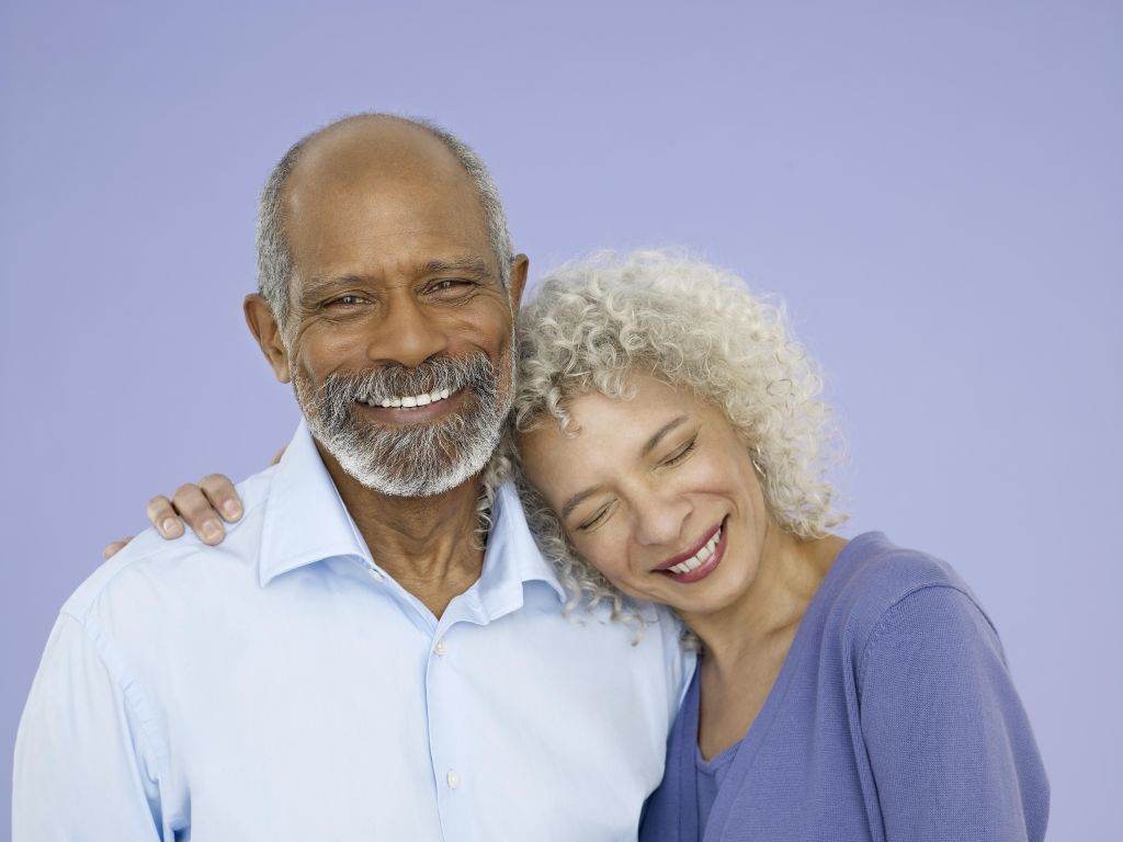 Mature woman and senior man huggin, man looking at camera, studio shot